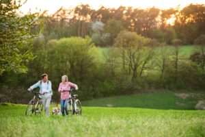 Beautiful senior couple with bicycles and dog outside in spring nature.