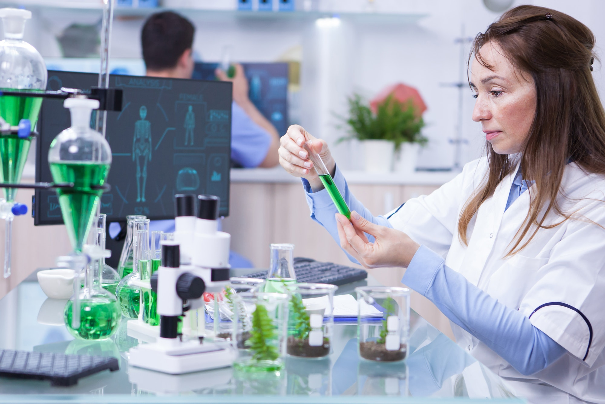 Side view of female scientist doing research on plants holding a green solution in a test tube