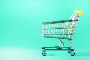 Shopping cart on blue background. Minimalism style. Creative design. Copy space. Shop trolley at