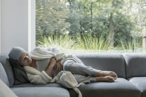 Weak elderly woman with cancer and stomach pain alone at home