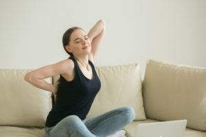 Woman pain neck head and back home sitting sofa